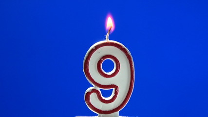 Number 9 - nine birthday candle burning