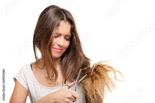 canvas print picture Young woman looking at split ends