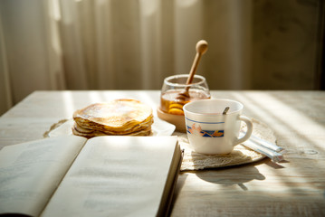 A cup of hot tea with honey pancakes and a book by the window