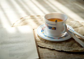 A cup of hot tea with a book by the window