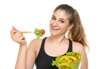 Ragazza felice di mangiare un'insalata