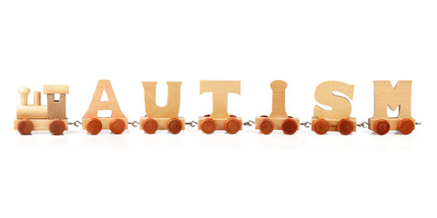 Autism spelled out in wooden train letters on white background