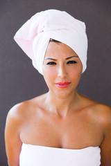 Woman in towel looks happy in camera