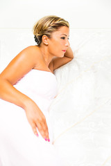 Woman wrapped in towel on the bed in the bedroom