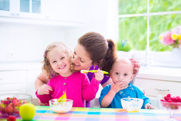 Happy mother and kids having breakfast