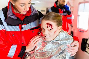 Notärzte helfen verletzte Frau in Krankenwagen