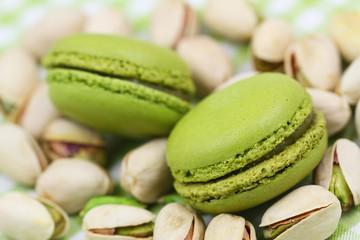 Pistachio macaroons on pistachio nuts, close up