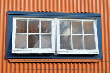 Old window on industrial building with corrugated metal walls