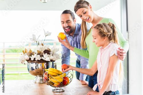 canvas print picture Familie isst frisches Obst für gesunde Ernährung