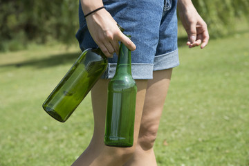 Woman's hand holding wine and beer bottles