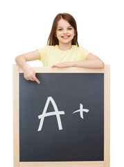 happy little girl pointing finger to blackboard