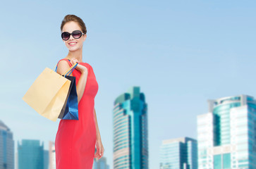 smiling woman in red dress with shopping bags