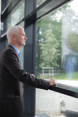 businessman looking out big window