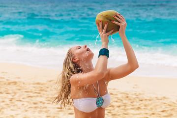 Young beautiful woman with long hair in white bikini, drinking c