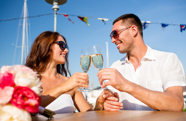 smiling couple drinking champagne at cafe