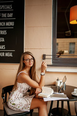 Young business woman in cafe drinking coffee with laptop