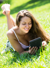 Girl lying on grass with tablet