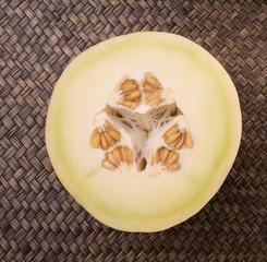 Half sliced honeydew fruit over wicker background