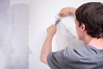 Heimwerker kratzt Tapete von der Wand