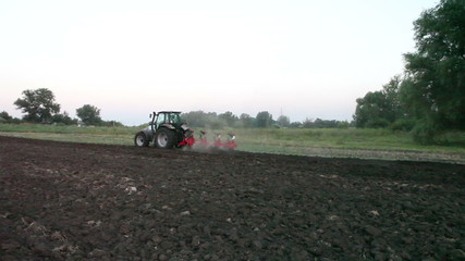 Tractor plowing the black earth plow field at sunset overgrown w