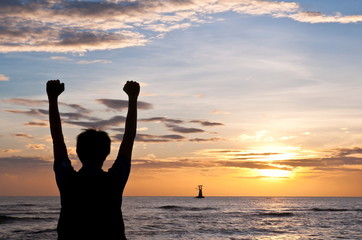 Successful man raising arms on the beach sunset