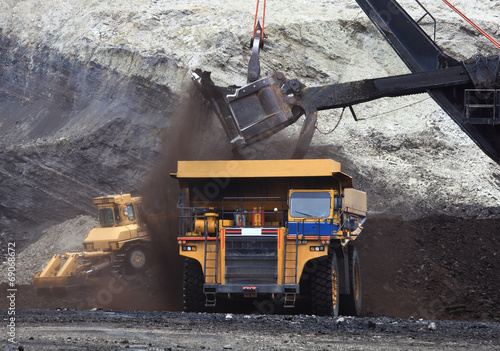Haul Trucks being loaded with ore. - 69068672