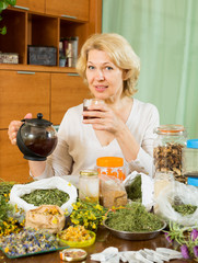 mature woman sitting at  table with herbs