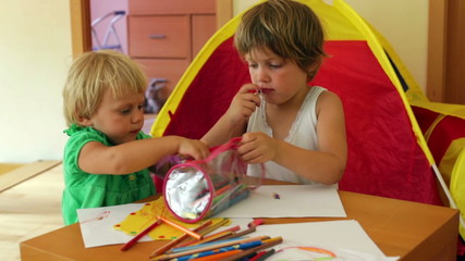 serious siblings playing with pencils in home interior