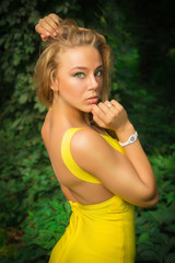 beautiful athletic girl in a yellow dress posing on a background