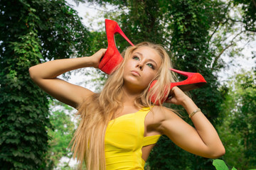 beautiful athletic girl in a yellow dress with red shoes in hand