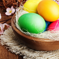 Easter eggs and branch with flowers on wooden
