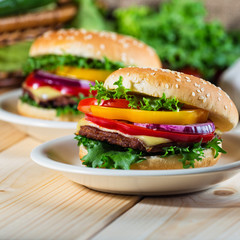 homemade hamburger with fresh vegetables on cutting board