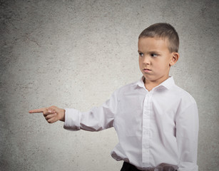 Unhappy boy pointing finger at someone, something