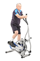 Mature man exercising on a cross trainer machine