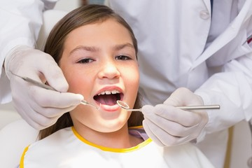 Pediatric dentist examining a patients teeth