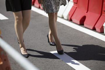 Women walk by wearing black shoes