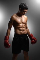 boxer with boxing gloves standing on grey background with spotli