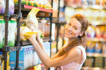 Happy woman shopping in a grocery store, buying bulk