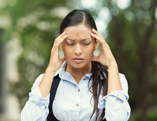 Stressed woman having headache, outside park background
