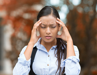 Stressed woman having headache, outside street background