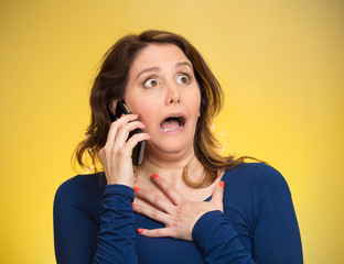 Woman receiving shocking news on phone, yellow background