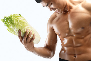A muscular guy and fresh vegetables,shaped abdominal, isolated o