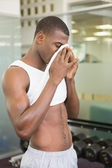 Fit man wiping sweat after workout in gym
