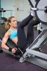 Fit woman doing leg presses in gym