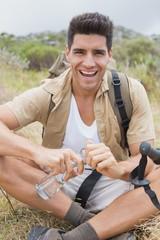 Cheerful hiking man sitting on mountain terrain