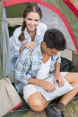 Couple using laptop in tent