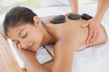 Beautiful brunette enjoying a hot stone massage