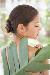 Beautiful brunette posing with palm leaf