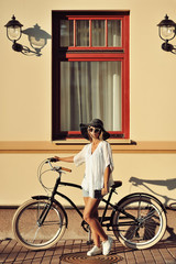 Fashion portrait of beautiful blonde on a vintage bicycle