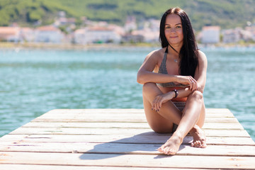 Young beautiful woman sitting at a pier